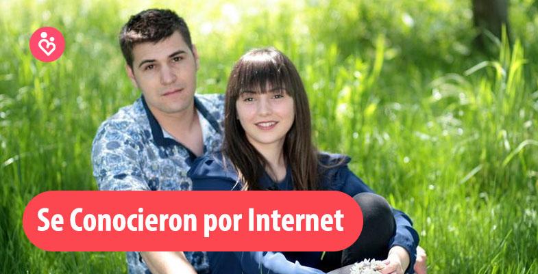 una pareja feliz sentada en el pasto